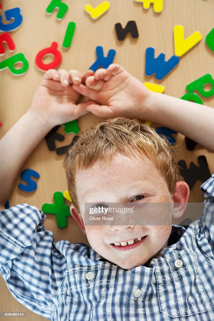 Boy lying next to alphabet letters : Stock Photo