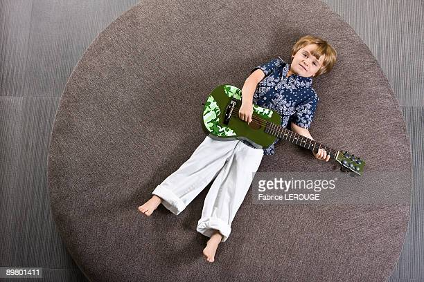 Boy lying on a round sofa and playing a guitar