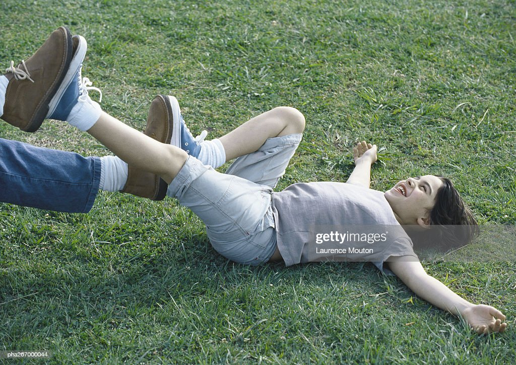 Boy lying on back on grass with feet pushing against man's feet : Stockfoto