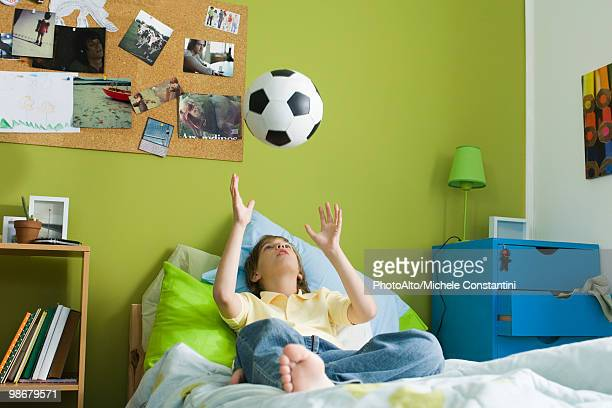 Boy lying on bed idly tossing ball into air