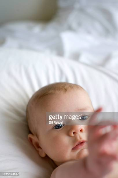 1 boy lying on bed reaching arm out
