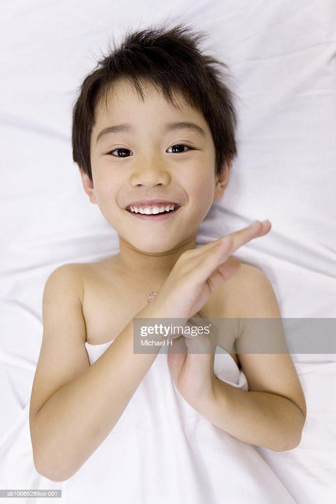 Boy (5-6) lying on bed, smiling, portrait : Foto stock