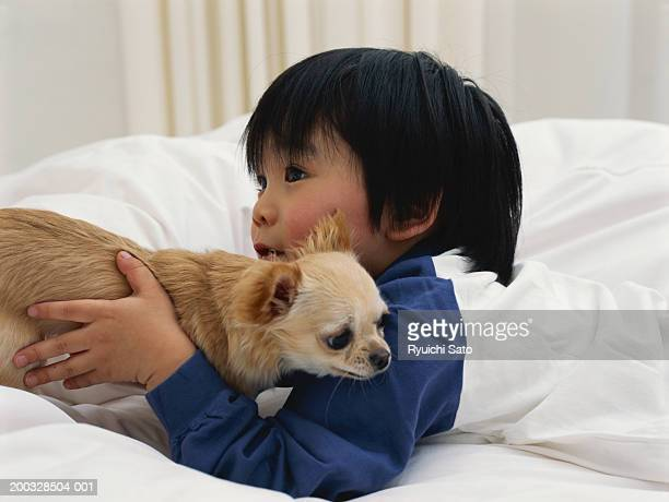 Boy (3-4) lying on bed with puppy, side view