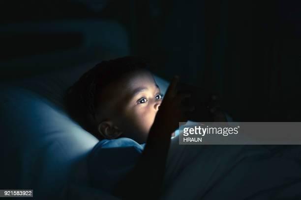 スマート フォン病棟でベッドに横たわっている少年