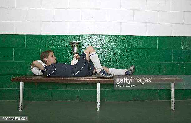 boy (8-10) lying on bench in change room, holding trophy - locker room stock pictures, royalty-free photos & images