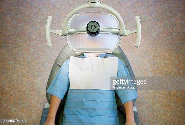 Boy (10-12) lying on dentist's chair, overhead view