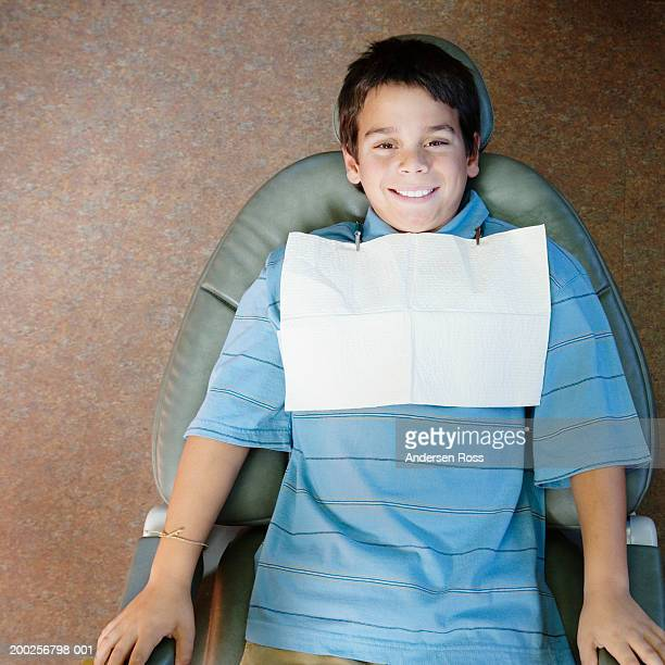 Boy (10-12) lying on dentist's chair, smiling, portrait, overhead view