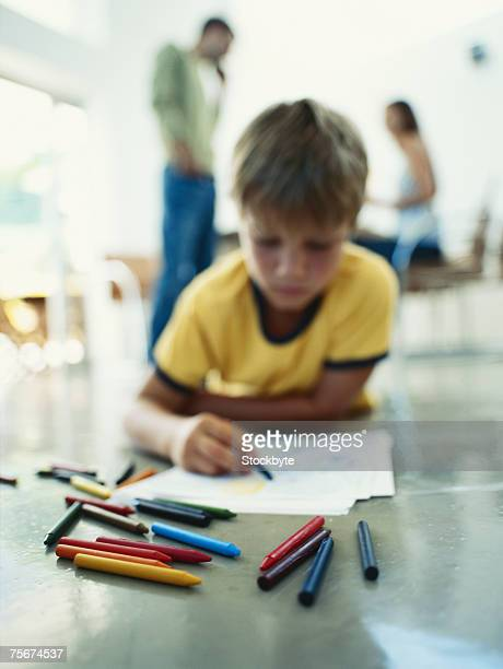 Boy (10-11) lying on floor and colouring with crayons, parents in background