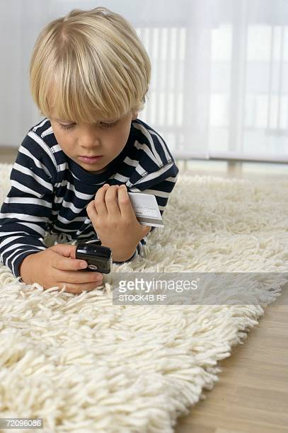 Boy (4-5 Years) lying on floor and holding a mobile phone and a credit card