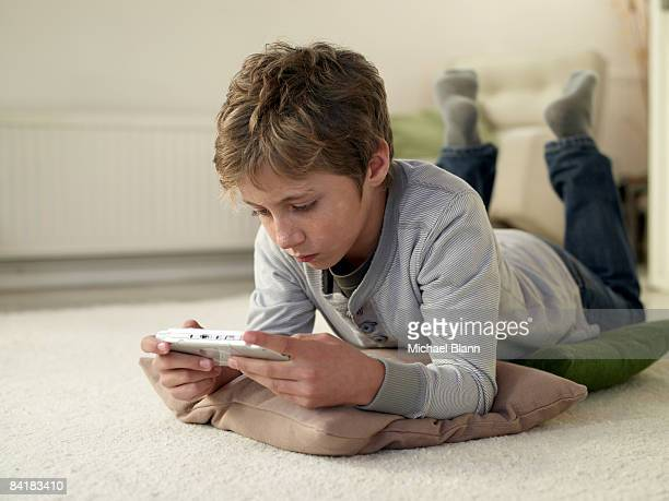 boy lying on floor at home playing computer game - handheld video game stock pictures, royalty-free photos & images