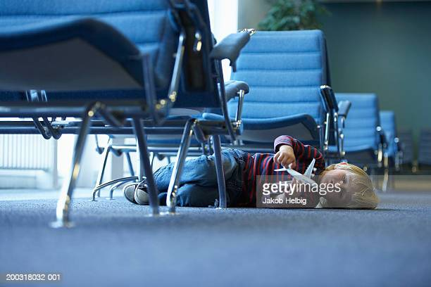 boy (3-5) lying on floor in airport lounge holding toy plane - kid in airport stock pictures, royalty-free photos & images