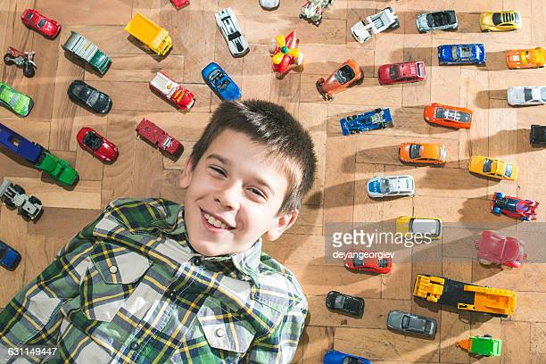boy lying on floor surrounded by toy cars - arrangement stock pictures, royalty-free photos & images