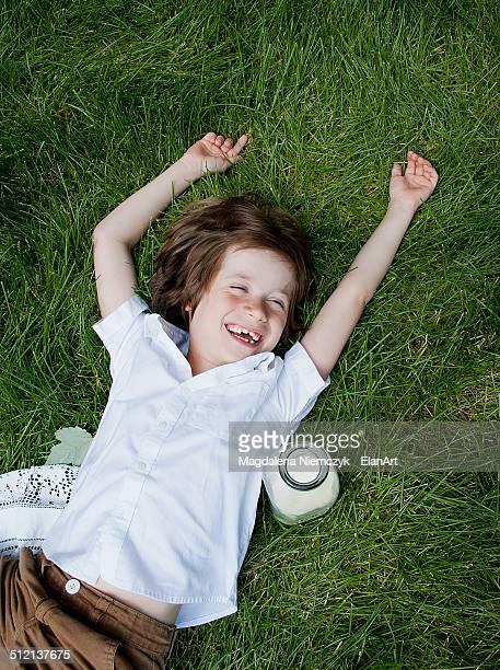 Boy lying on grass laughing