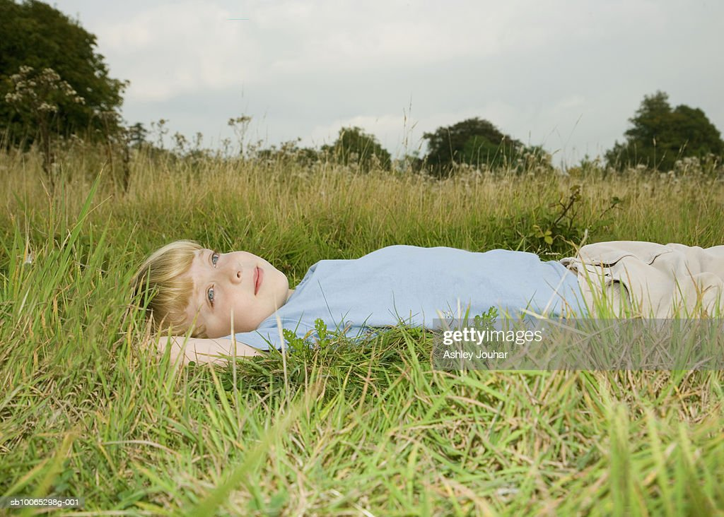 Boy (6-7) lying on grass, looking up at sky : Foto stock