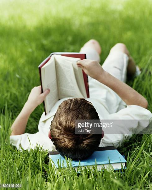 Boy (6-8) lying on grass reading book, rear view