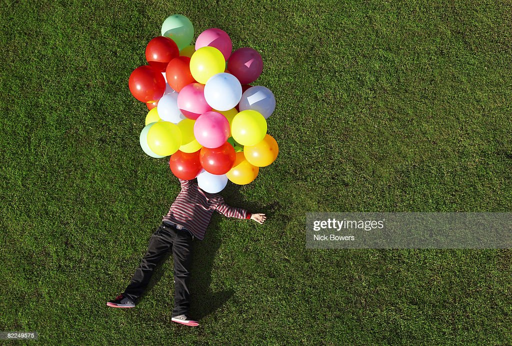 Boy lying on grass with balloons : Stock Photo