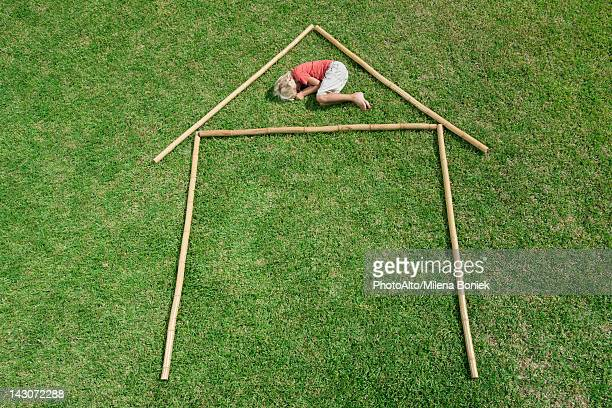 Boy lying on grass within outline of house, high angle view