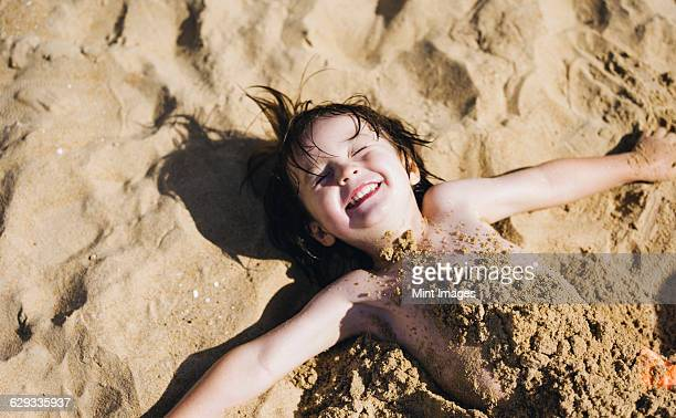 A boy lying on his back on the beach, his torso covered in sand, laughing.