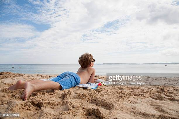 A boy lying on his front on the sand looking out to sea.