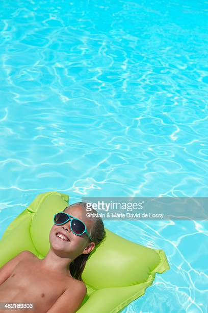 Boy lying on inflatable mattress in swimming pool