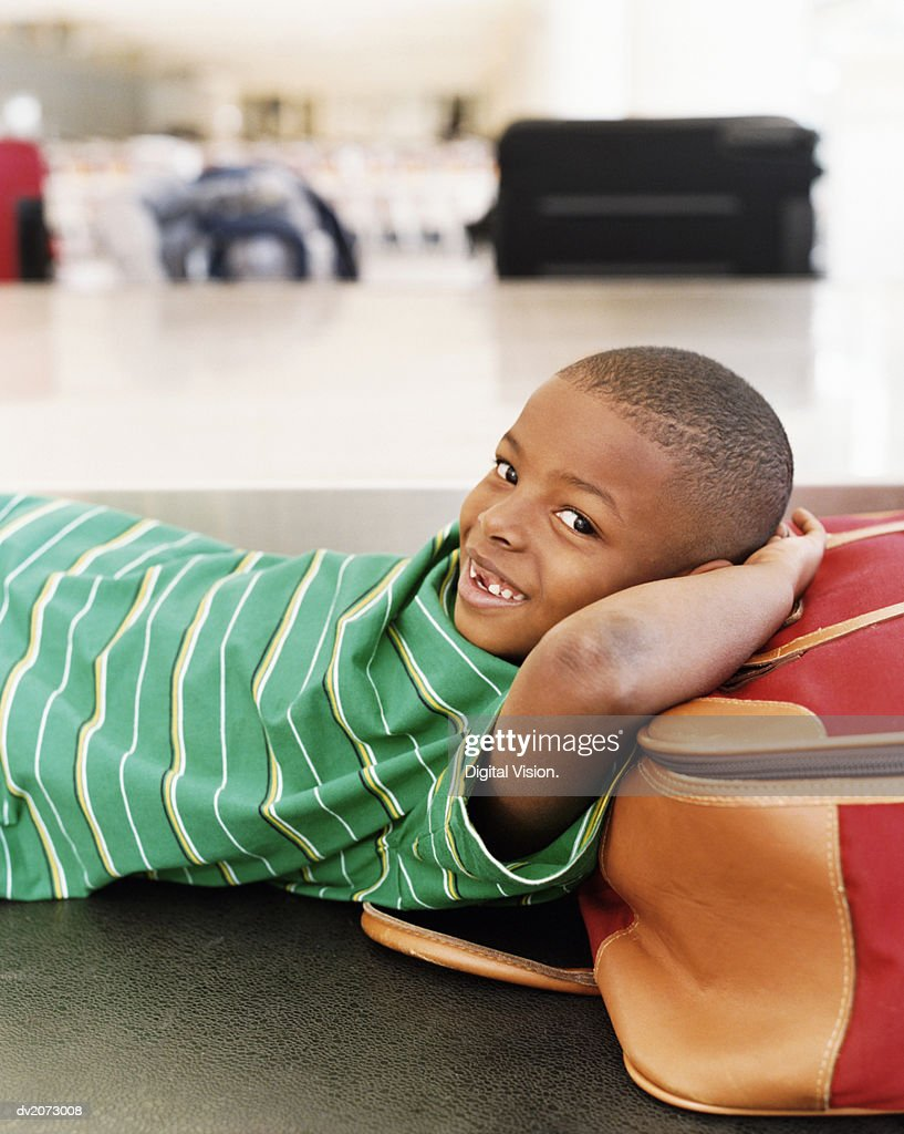 Boy Lying on Luggage on an Airport Baggage Conveyor Belt : Stock Photo