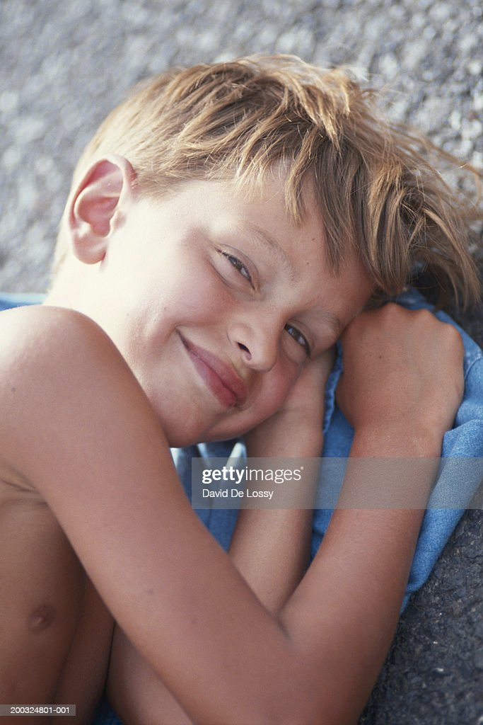 Boy Lying On Side Smiling Elevated View High-Res Stock