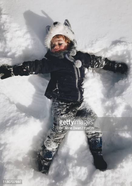 boy lying on snowy field - brianne stock pictures, royalty-free photos & images