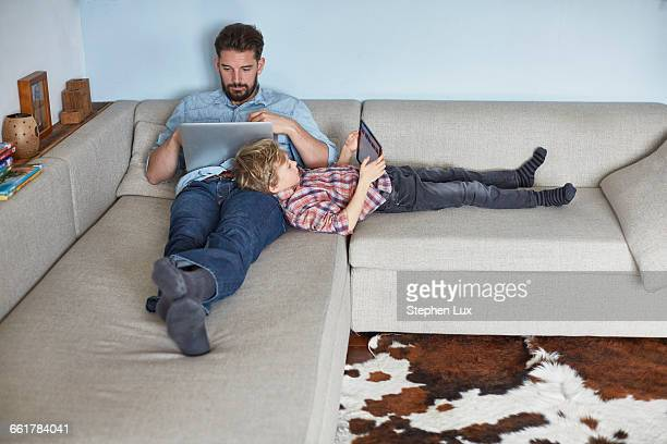 boy lying on sofa with father using technology - smooth stock pictures, royalty-free photos & images