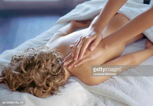 boy (8-9) lying on stomach, having back massage - naakte jongens stockfoto's en -beelden