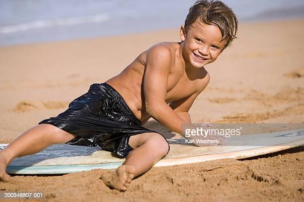 Boy (5-7) lying on surfboard, on beach, smiling
