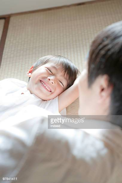 boy lying on tatami mat with his father, smiling - newhealth stock pictures, royalty-free photos & images