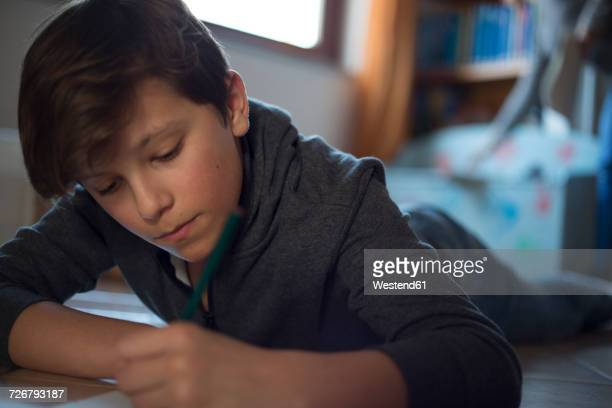 Boy lying on the floor at home doing homework