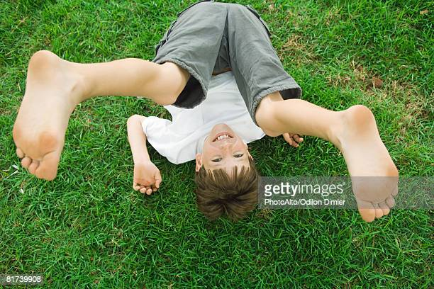 Boy lying on the ground with legs in the air, smiling at camera, high angle view