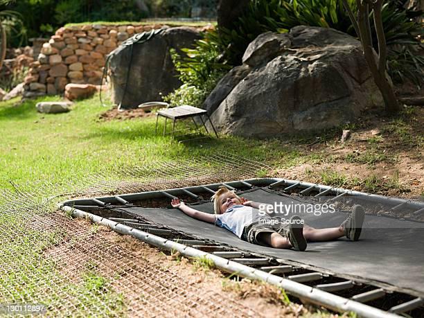Boy lying on trampoline