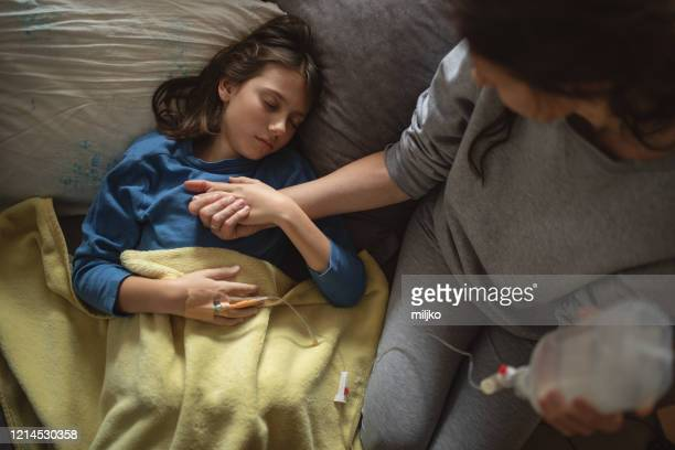 boy lying sick on sofa and his mother taking care for him - infused stock pictures, royalty-free photos & images
