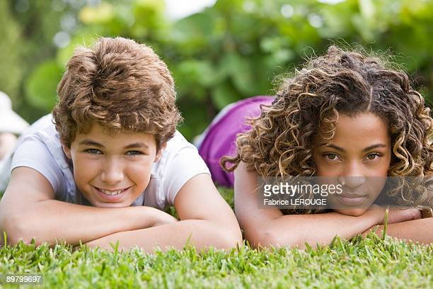Boy lying with his sister in a garden