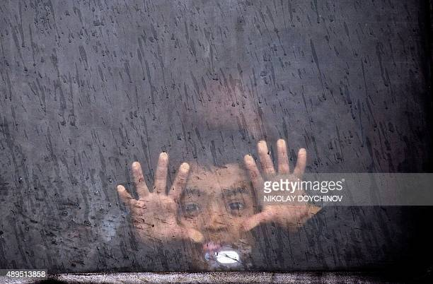 A boy makes a grimace aboard a train transporting migrants and refugees to Serbia after they crossed the GreekMacedonian border near Gevgelija on...