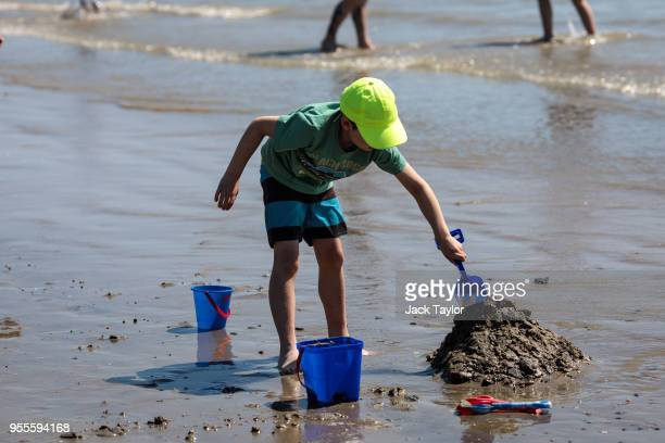 A boy makes sand castles with a bucket and spade on the beach during the warm weather on Bank Holiday Monday on May 7 2018 in Bognor Regis United...