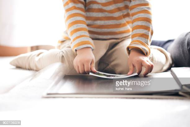 boy making a photo album - childhood photo album stock photos and pictures