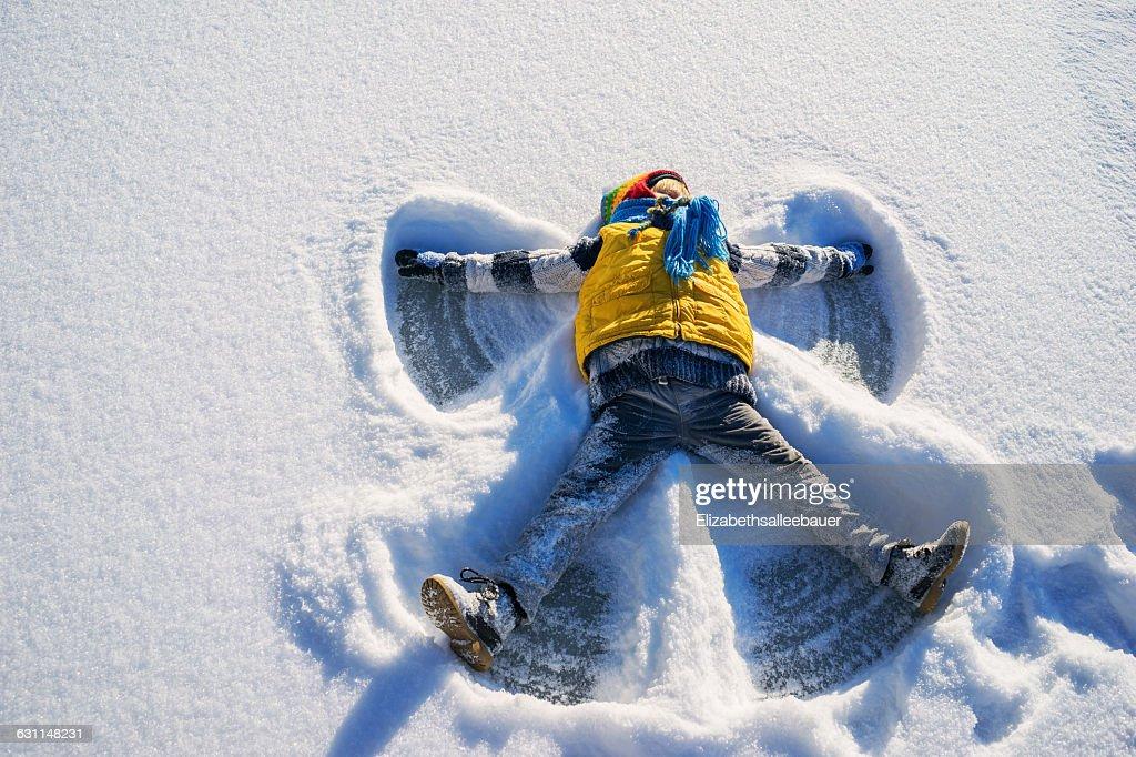 Boy making a snow angel : Stock Photo