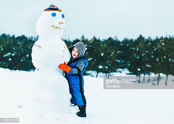 A boy making a snowman