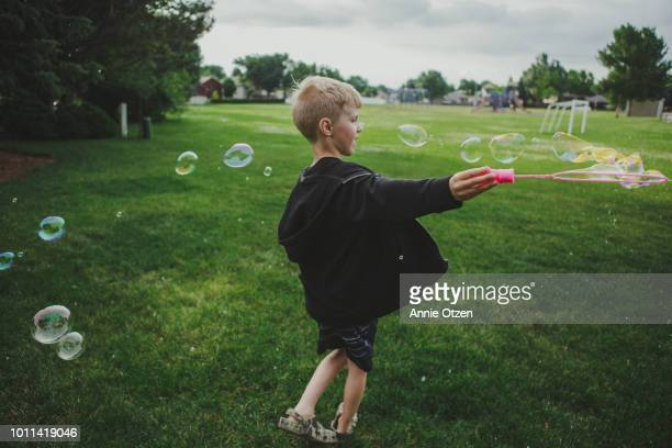 boy making bubbles - annie sprinkle stock pictures, royalty-free photos & images