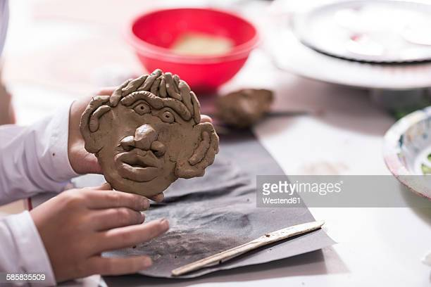 Boy making face from modeling clay in art class at school