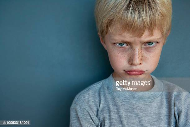 Boy (8-9 years) making face, studio shot, portrait