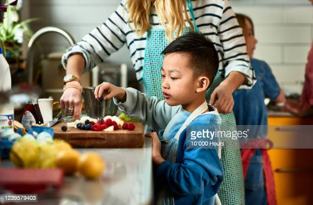 boy making fruit salad in kitchen with mother - asian and indian ethnicities stock pictures, royalty-free photos & images