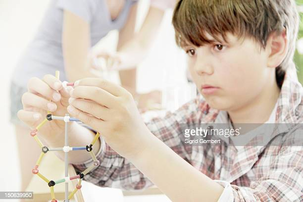 Boy making molecular model in class
