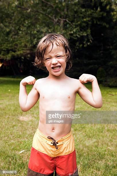 boy (4-5) making muscles