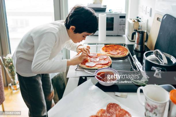 boy making pizza at home - peter lourenco stock pictures, royalty-free photos & images