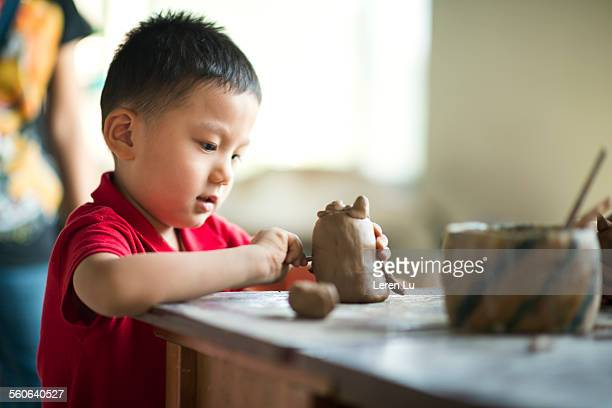Boy making pottery clay and carving