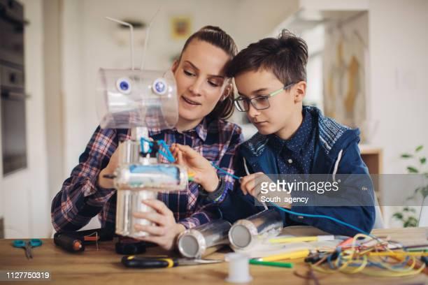 boy hacer robot de juguete para el proyecto de la escuela con su hermana - montar fotografías e imágenes de stock